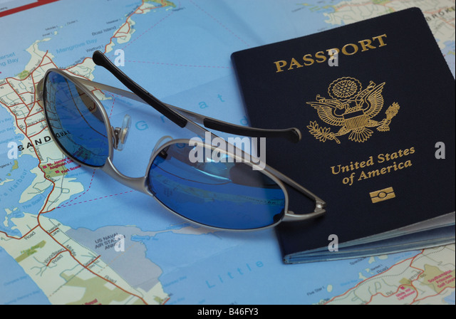 A United States Passport, sunglasses, and a folded map of Bermuda illustrate the concept of travel. - Stock-Bilder