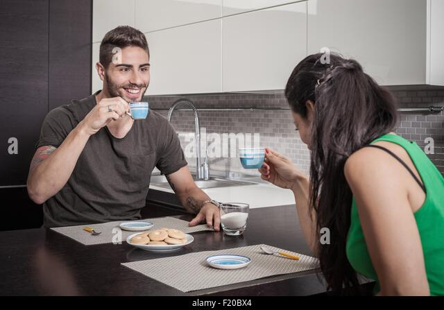 Young couple drinking coffee at breakfast bar - Stock Image