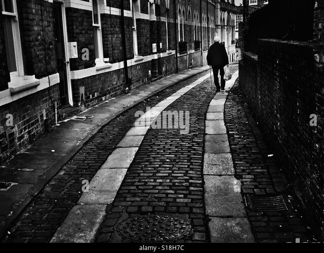 Old man walking down cobbled lane in York - Stock-Bilder