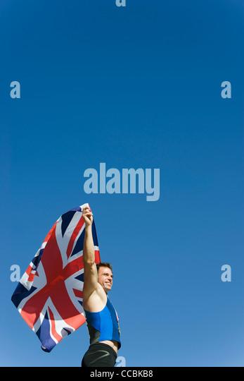 Male athlete holding up British flag - Stock Image