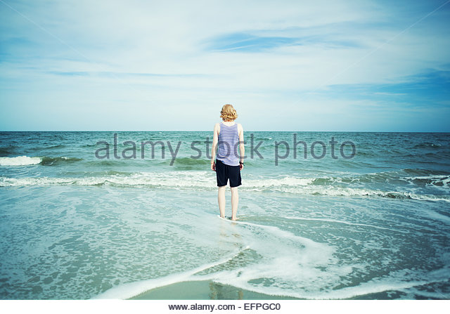 Young man standing in sea - Stock Image