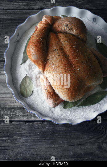 Raw Thanksgiving day turkey with spices on the baking dish with salt and bay leaf vertical - Stock Image