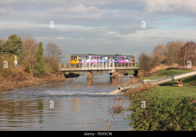 "A Northern train service formed of a ""Pacer"" train crosses the River Douglas in Rufford - Stock Image"