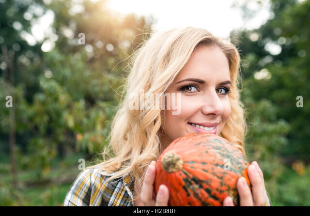 Beautiful young blond woman in her garden harvesting pumpkins - Stock Image