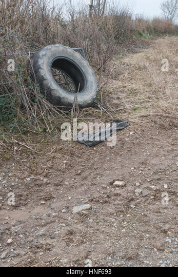 Tractor tyre propped up beside the gated entrance to a field. - Stock Image