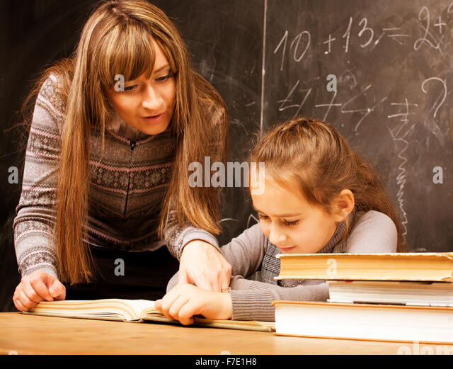 teacher with pupil in classroom at blackboard writting, girl at school - Stock Image