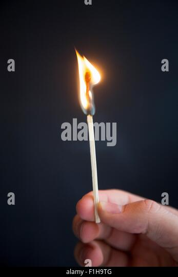 Person holding burning match - Stock Image