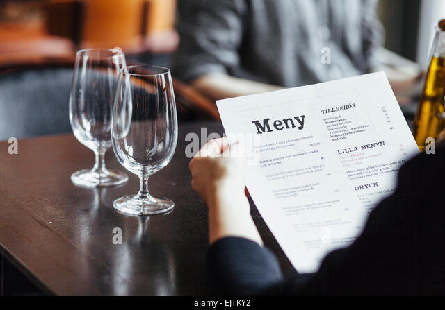 Cropped image of woman holding menu while sitting with man in restaurant - Stock-Bilder