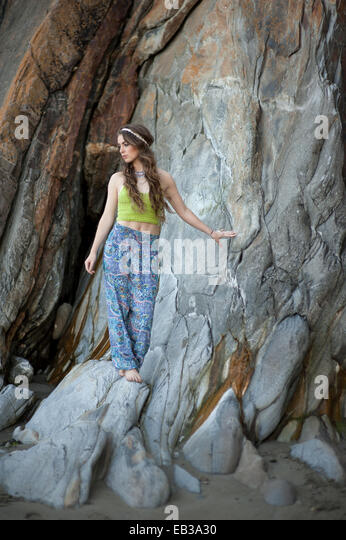 Young woman standing on rocks on beach - Stock Image