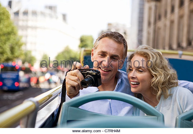 A middle-aged couple sitting on a sightseeing bus, holding a camera - Stock Image