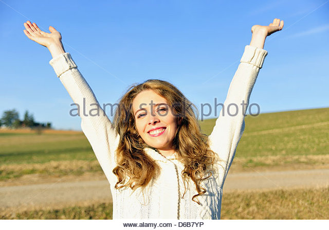 Woman cheering in rural field - Stock Image