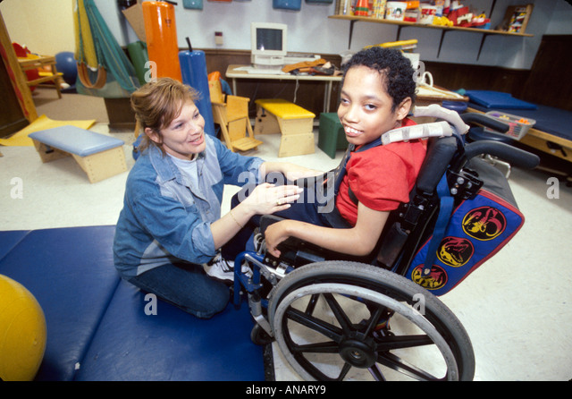 New Jersey East Orange Cerebral Palsy Center disabled student female therapist Hispanic boy wheelchair - Stock Image