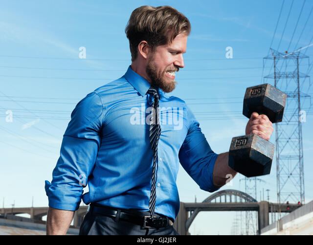 Businessman weightlifting, Los Angeles river, California, USA - Stock Image