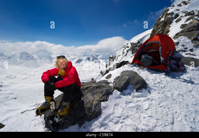 A mountaineer relaxing on a rock after a hard days climbing. - Stock Image