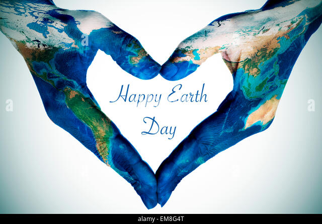 the hands of a young woman forming a heart patterned with a world map (furnished by NASA) and the text happy earth - Stock Image