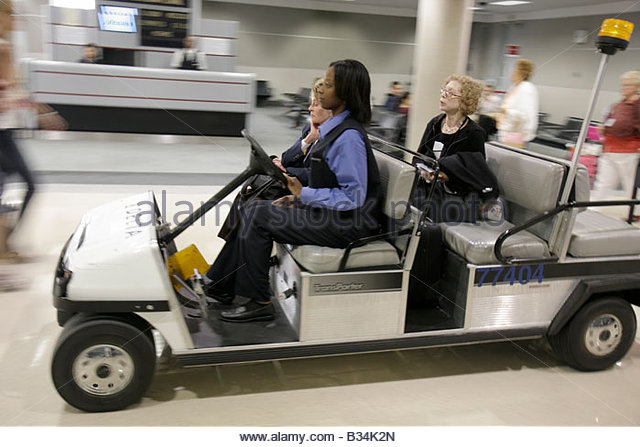 Atlanta Georgia Hartsfield International Airport concourse Black woman women senior assistance courtesy cart transport - Stock Image