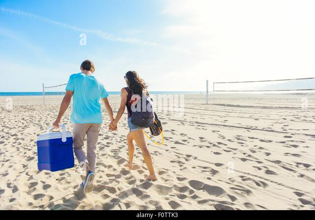 Young couple walking on beach, holding cool box, rear view - Stock-Bilder