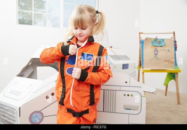 Young girl playing dress up, wearing astronaut outfit - Stock Image