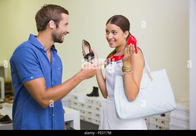 Young couple deciding on which shoe to choose - Stock Image