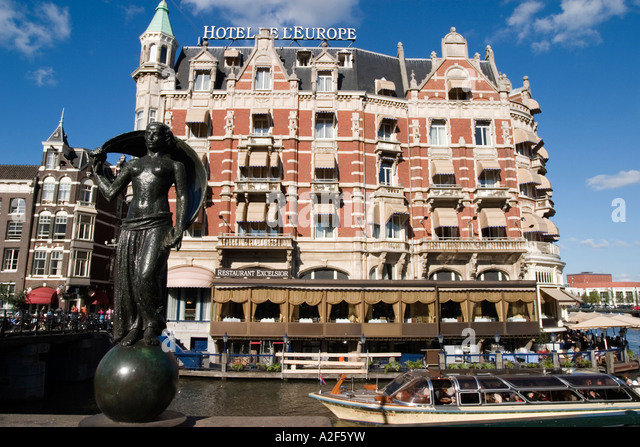 Amsterdam Hotel de l Europe canal sculpture canal boat Restaurant Exelsior Terasse - Stock Image