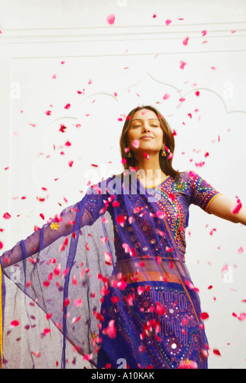Close-up of a young woman standing with rose petals falling around her - Stock-Bilder