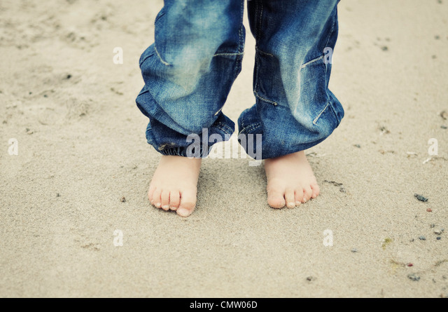 Low section of a boy at beach - Stock Image