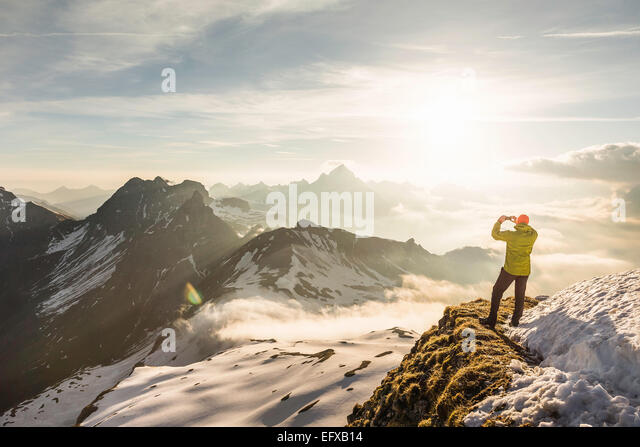 Young male mountain trekker photographing view of clouds, Bavarian Alps, Oberstdorf, Bavaria, Germany - Stock-Bilder