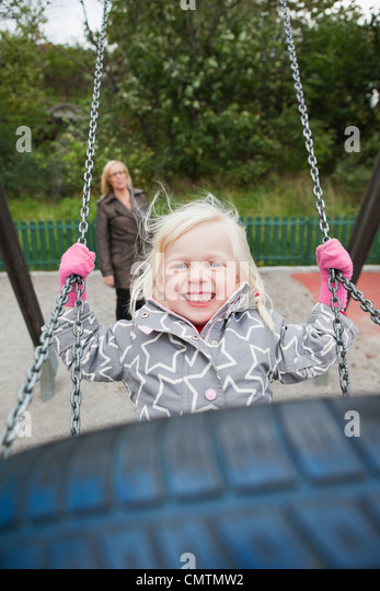 Joyful girl (2-3) with mother in background - Stock Image