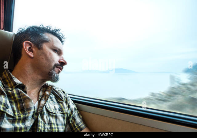 A man looking out a window on a train traveling near water. - Stock Image