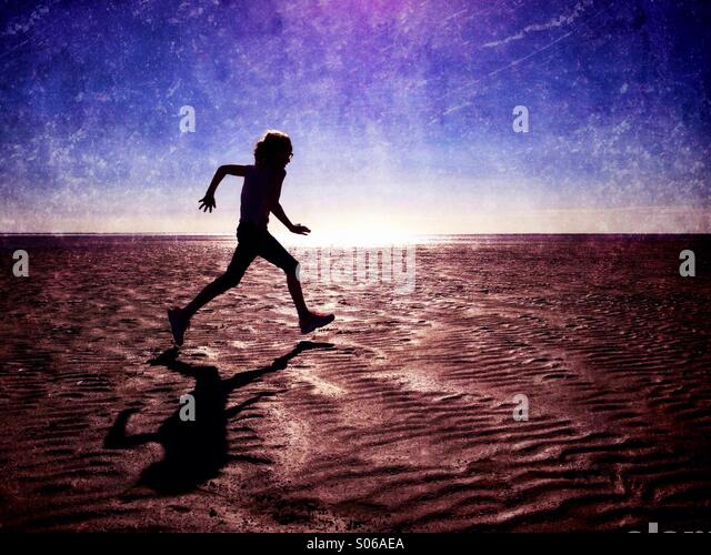 Girl in silhouette running on empty beach - Stock Image