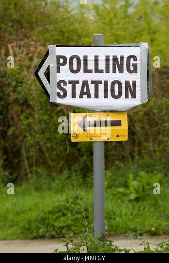 Polling station sign on a road direction arrow - Stock Image