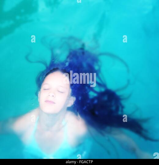 High Angle View Of Young Woman With Eyes Closed In Swimming Pool - Stock Image