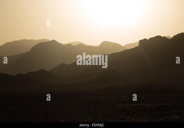 Intense colours amplified by dust at sunset in Hamedila, Ethiopia. This line of hills is a fossilised coral reef, - Stock Image