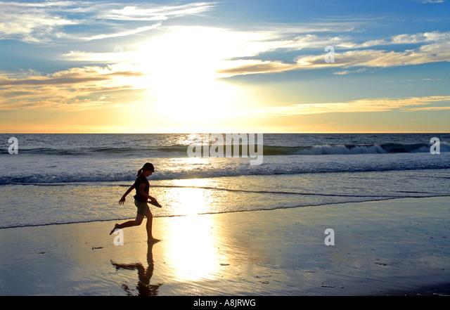 Girl running on beach - Stock-Bilder