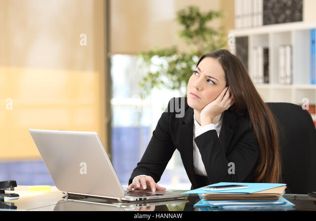 Worried pensive businesswoman looking sideways in a desktop at office - Stock Image