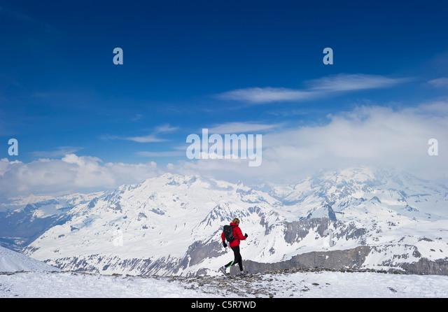 Jogger running through snowy mountain range. - Stock-Bilder