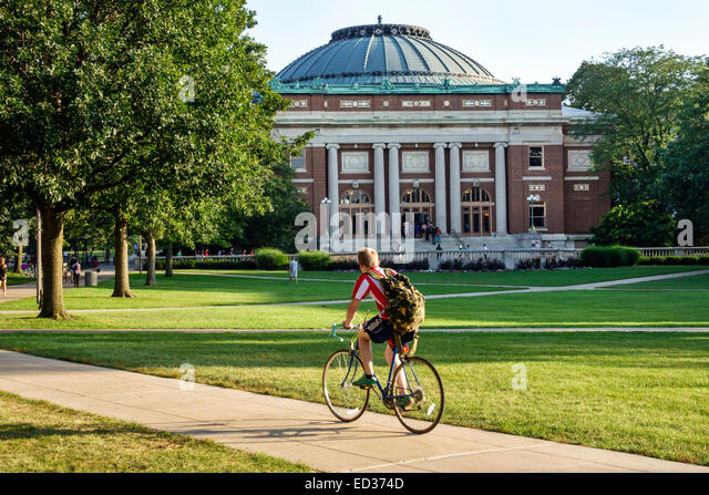 Illinois Urbana-Champaign University of Illinois campus student man teen boy Foellinger Auditorium riding bicycle - Stock Image