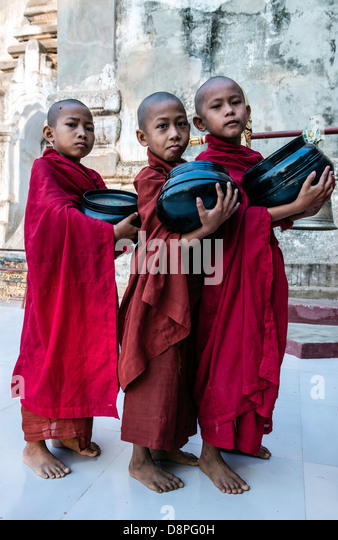 Novice Buddhist monks collecting alms bowls of food in the morning from villagers near Bagan Burma Myanmar - Stock-Bilder