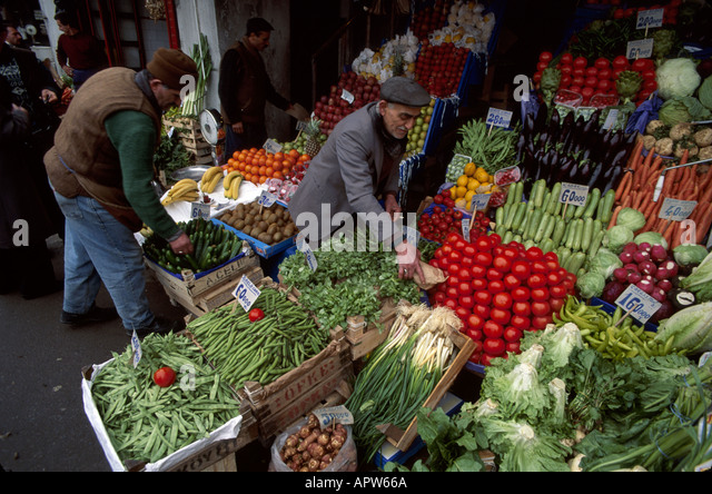 Turkey Europe Asia Istanbul Eminonu Quarter Muslim man produce display stand food vegetables fruits - Stock Image