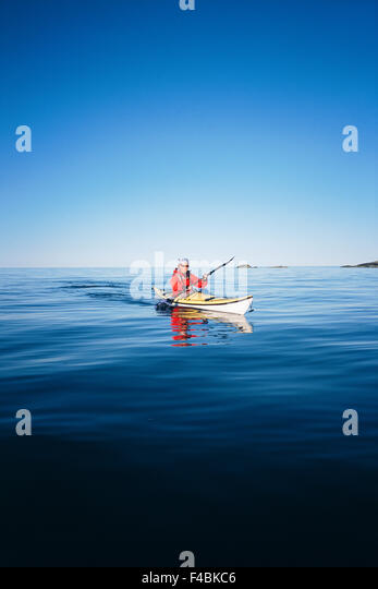blue boat canoe clear sky color image freedom kayak life on sea nature one person only outdoors paddling sea sky - Stock-Bilder