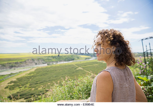 Smiling woman looking at view of countryside - Stock Image
