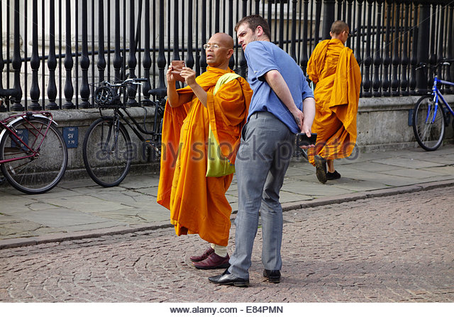 A buddhist seeks advice about using his camera from another tourist on Kings Parade in Cambridge, England, UK - Stock-Bilder