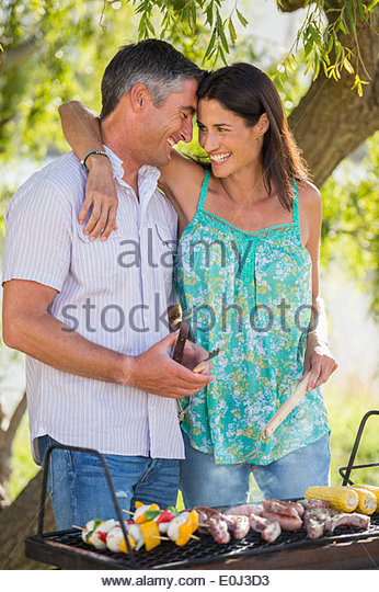 Couple Cooking Barbeque In Countryside - Stock Image