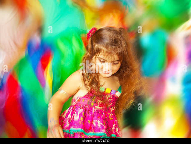 Adorable small girl dancing over blur colors background, three-year birthday girl, little happy kid enjoying child - Stock Image