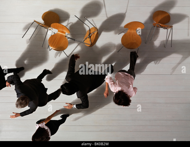 Business people knocking over chairs - Stock Image