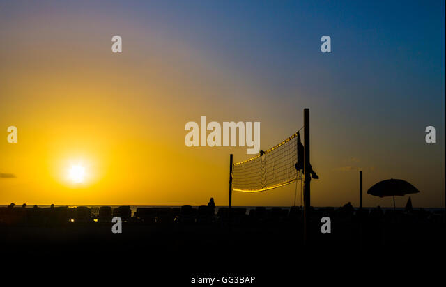 Beach volleyball net illuminated by the golden light of the setting sun, Jolly Harbour, south-west Antigua - Stock Image
