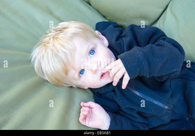 Overhead view of boy lying on garden chair - Stock Image