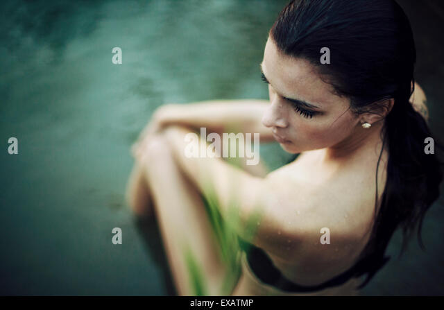 young woman sits in the water - Stock Image
