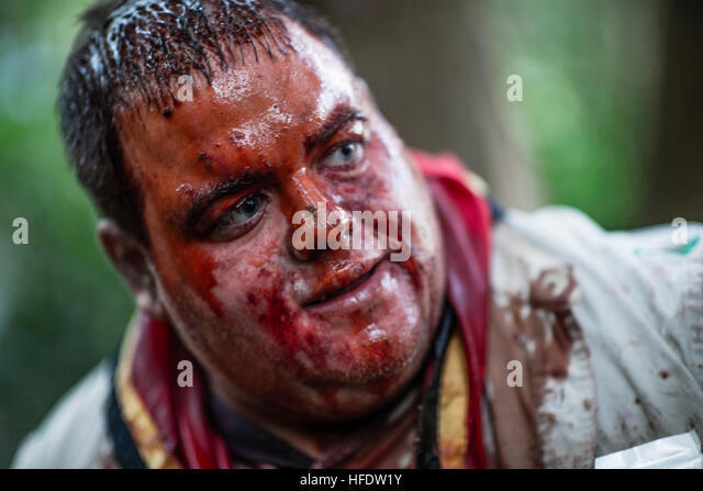 A man dressed and made up with a bloody  face as a zombie in the woods in a 'The Walking Dead Experience' - Stock Image