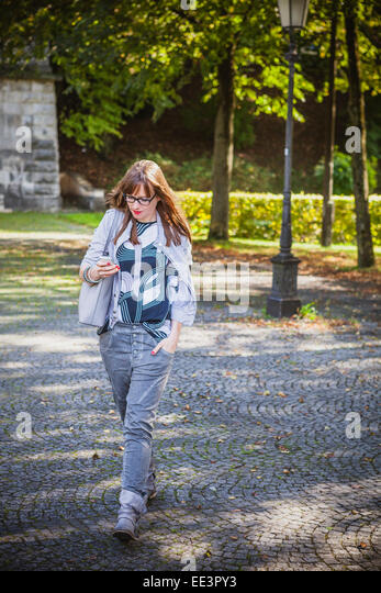 Young woman text messaging outdoors, Munich, Bavaria, Germany - Stock-Bilder